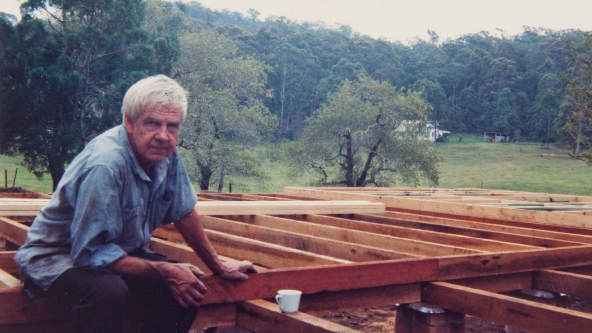 Arthur Boyd sitting on wooden beams at a construction site