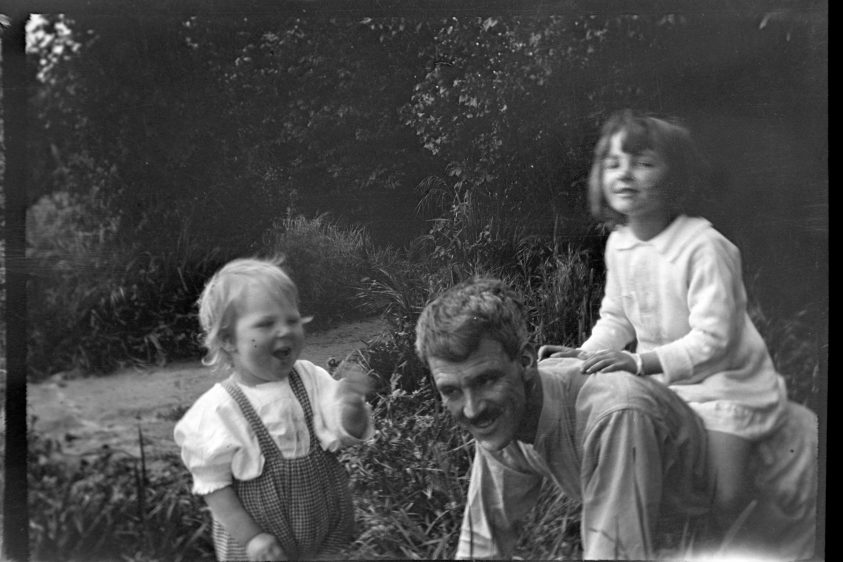 Photograph of a man and two young children playing outside