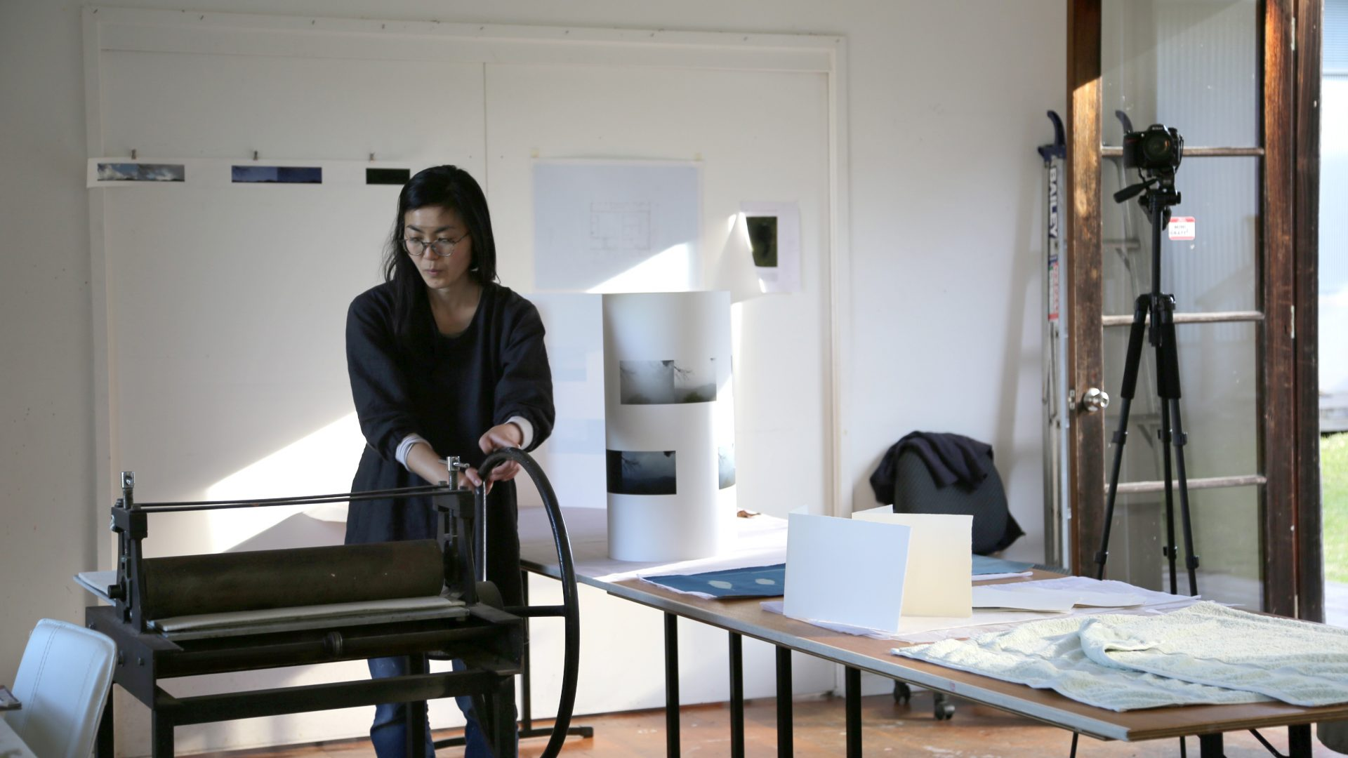 A person is standing in a studio working with a printing press
