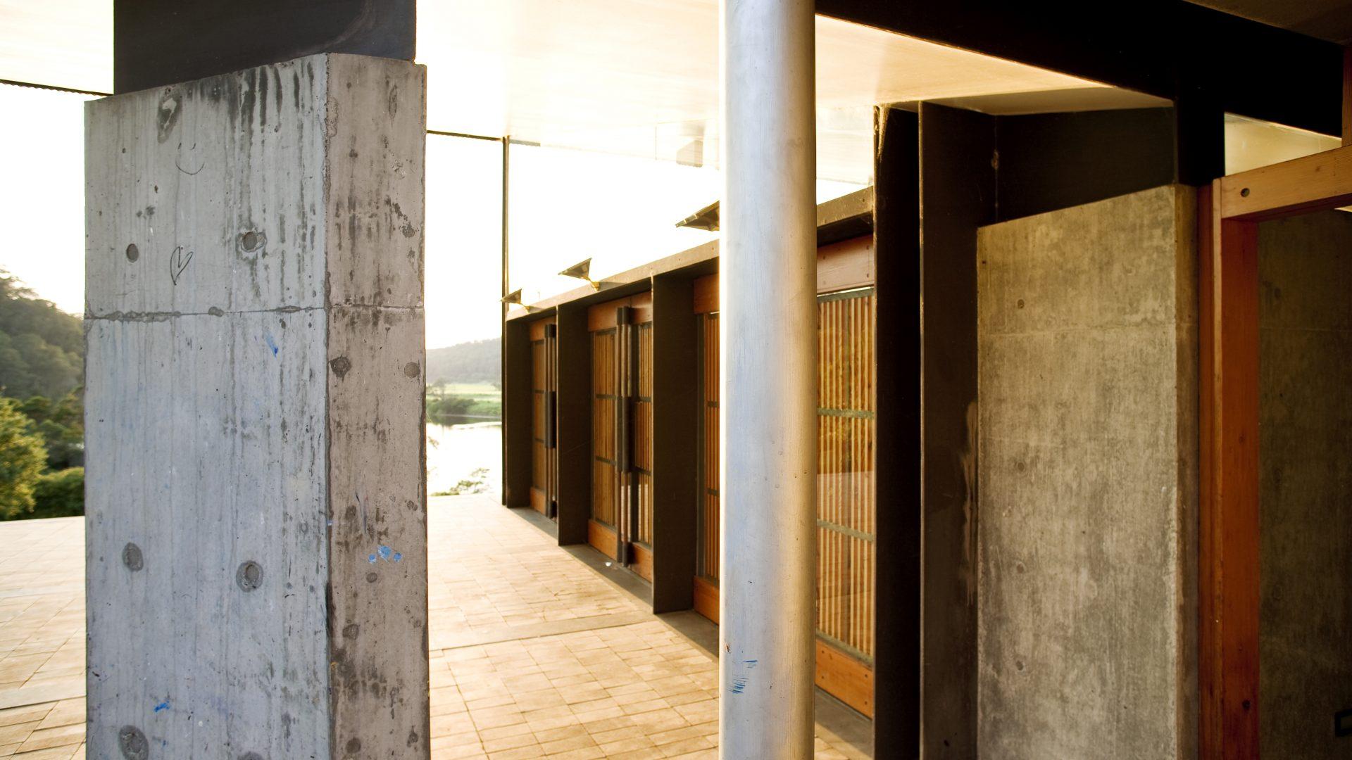 A concrete pylon and concrete wall behind