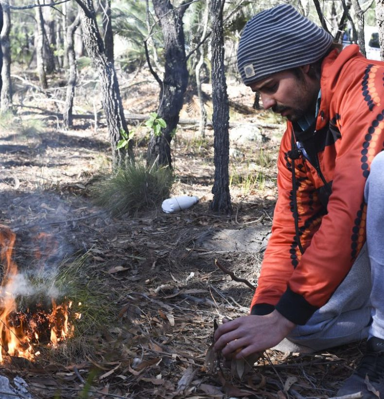 Person kneeling in a forest landscape with a small fire burning beside them