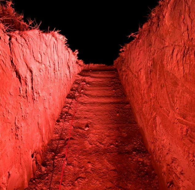 Photo of trench dug into ground illuminated with red light