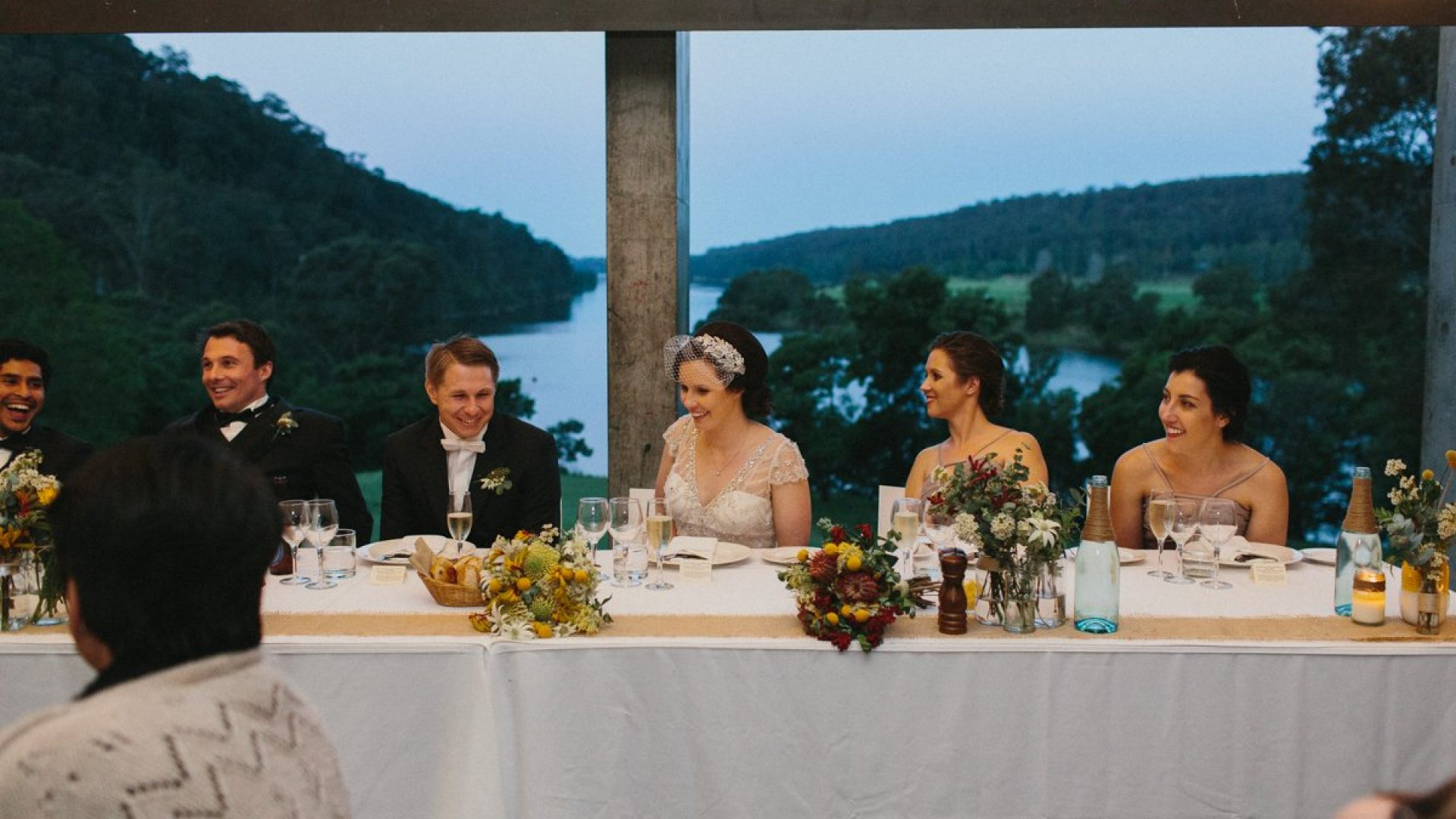 6 people sitting at a long table together. A river can be seen out the window behind them