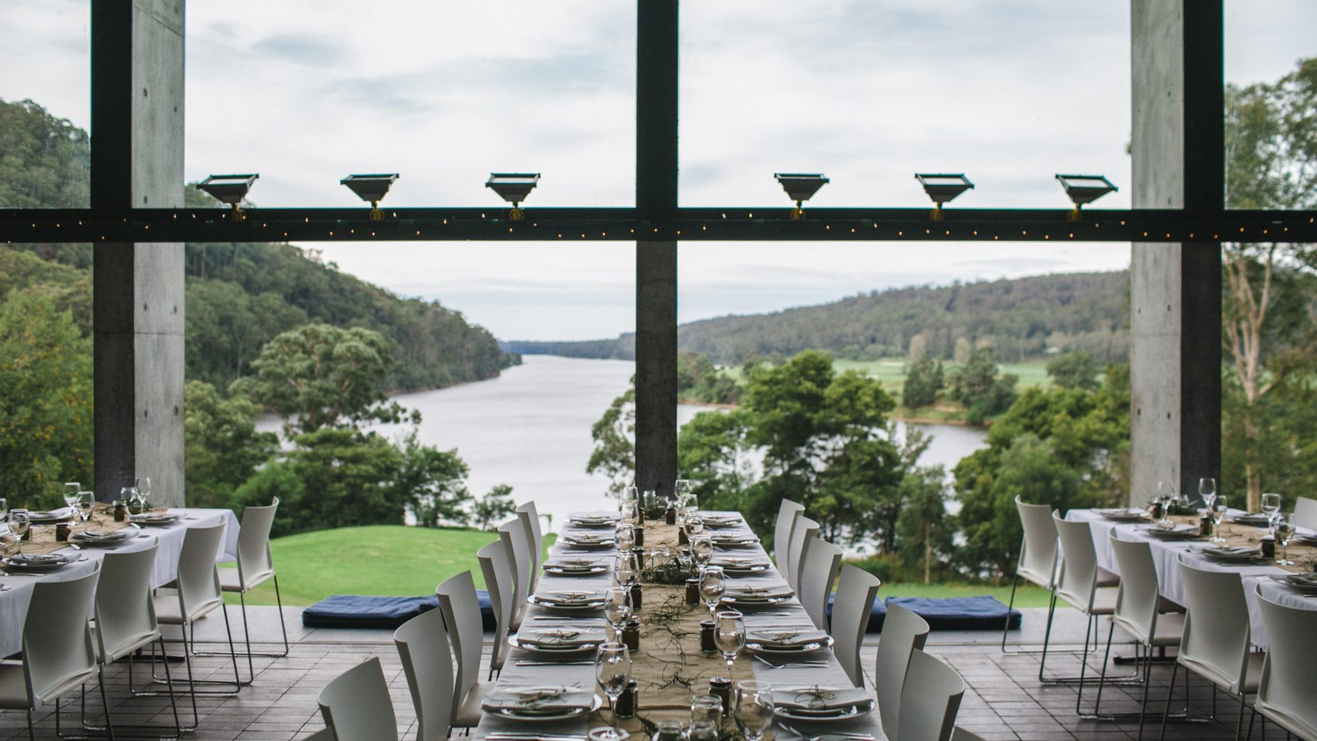 Rows of set dining tables in a room with a large window overlooking a river and mountains.
