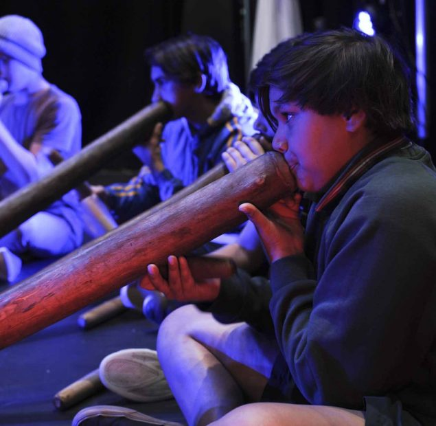 5 young boys playing the didgeridoo
