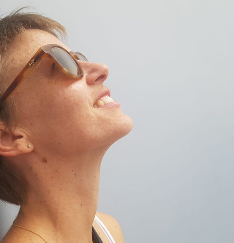 A person wearing sunglasses tilts their head to look above