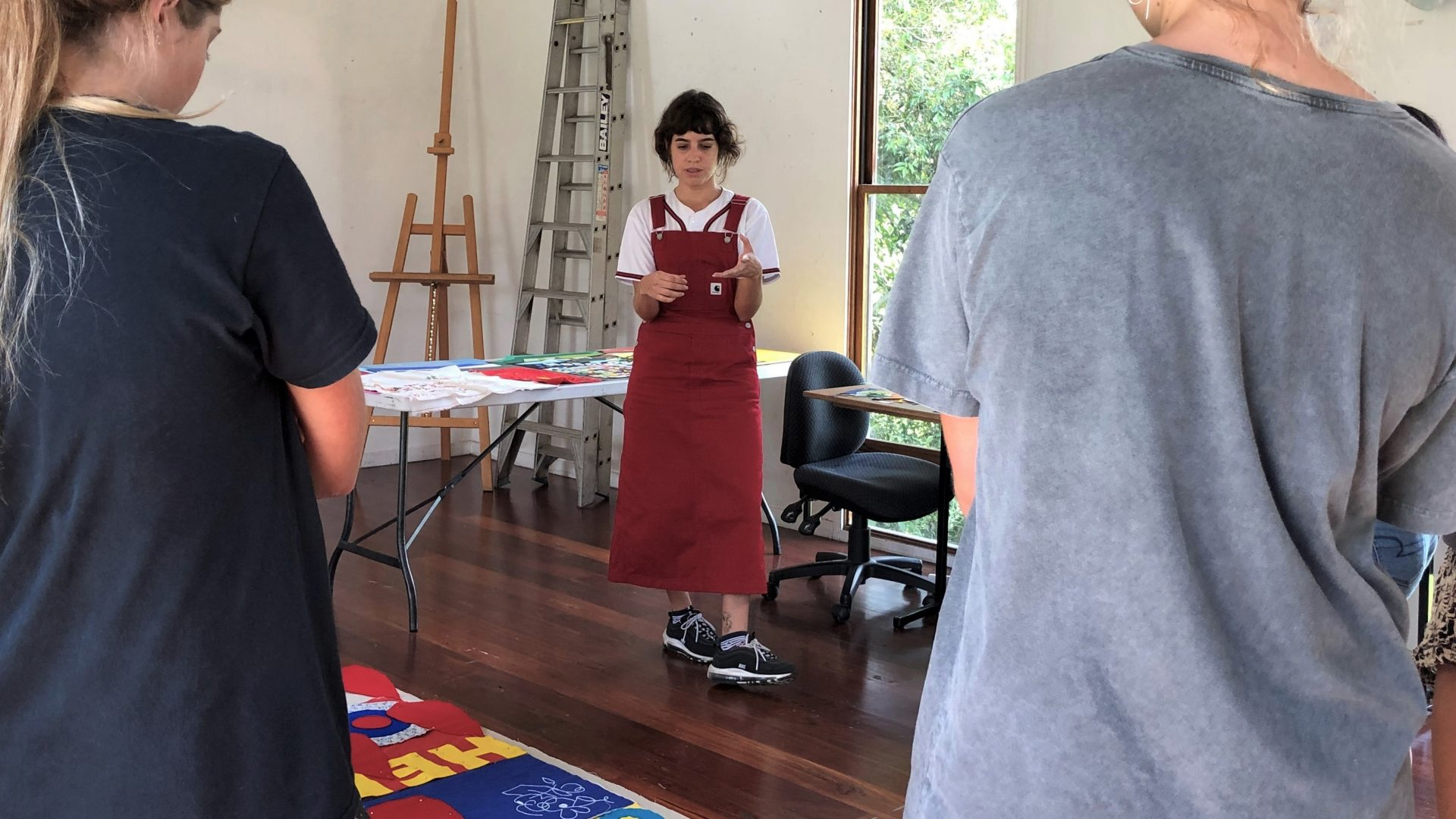 Person standing in front of two students. They are in an artist studio looking at colourful artworks on the ground